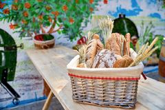 Bread basket outdoors on a wooden table in a street cafe, closeu Stock Images
