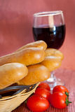Bread and wine. Bread in basket with some fresh tomato and Royalty Free Stock Images