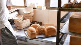 Bread Being Cooled on Tray in Bakery. A worker taking bread out of hot pans in order to cool them. Loaves of freshly baked bread is put in racks on bread stock video