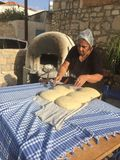 Bread being made in an old stone kiln. A lady making bread in an outdoors kiln Royalty Free Stock Photos