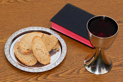 Bread, Bible and Chalice on wood table Royalty Free Stock Photography