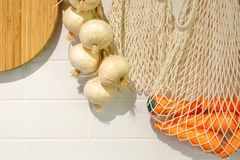 Bread bin. View of the kitchen counter with cutting Board, hanging on the wall a few heads of garlic stock photography
