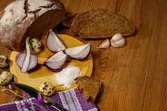 Bread black head of garlic and onion halves knife and fork Stock Photos