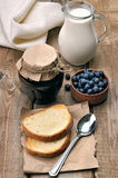 Bread, blueberry jam and milk on wooden table Royalty Free Stock Photography