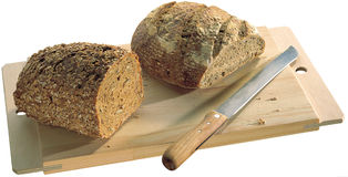 Bread on board. With knife Stock Images
