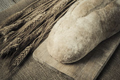 Bread on Bread Board with Wheat on Burlap Royalty Free Stock Images