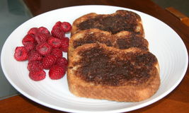Cinnamon toast with raspberries. Bread broiled with cinnamon and brown sugar and raspberries on the side Stock Photos