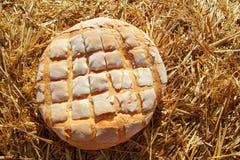 Bread bun round on golden wheat straw royalty free stock photography