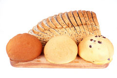Bread and Buns. Sliced wheat bread and buns on cutting wooden board for breakfast stock photography
