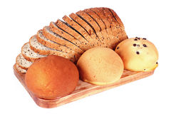 Bread and Buns. Sliced wheat bread and buns on cutting wooden board for breakfast royalty free stock images