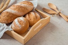 Bread and buns on wooden tray Stock Images