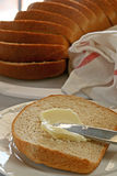 Bread and Butter. Slice of freshly baked bread with butter; remaining sliced loaf in background Royalty Free Stock Photography