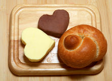 Bread and Butter. Baked hard roll is set on cutting board with hearts of butter and chocolate butter royalty free stock photos