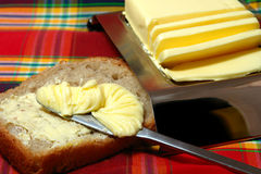 Bread and Butter. Slice of whole wheat bread, and knife spreading butter, sliced butter on tray nearby, red plaid tablecloth stock images