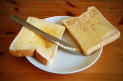 Bread and butter. Two pieces of bread with butter and a knife in a wooden table Stock Photography