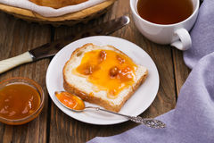 Bread with butter, apricot jam and a Cup of black tea Stock Photography