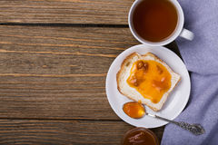 Bread with butter, apricot jam and a Cup of black tea Royalty Free Stock Photos
