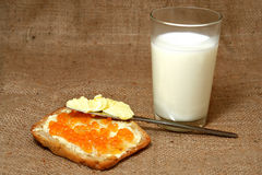Bread,Butter,Caviar,Milk. Snack laid out on burlap cloth: slice of bread with butter and red caviar, glass of milk royalty free stock photo