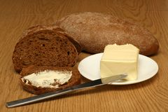 Bread and butter close-up. On the wooden table royalty free stock photos