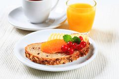 Bread with butter, cup of tea and orange juice Stock Photos