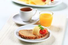 Bread with butter, cup of tea and orange juice Royalty Free Stock Image