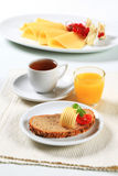 Bread with butter, cup of tea and orange juice Royalty Free Stock Photography