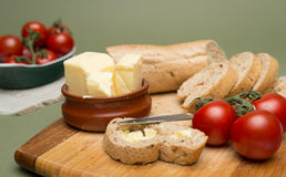 Bread and butter/Delicious organic home-made bread and butter with ripe tomatoes on wooden board. Royalty Free Stock Photos