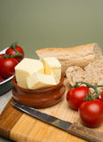 Bread and butter/Delicious organic home-made bread and butter with ripe tomatoes on wooden board. Bread and butter/Delicious organic home-made bread and butter royalty free stock photo