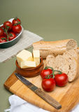 Bread and butter/Delicious organic home-made bread and butter with ripe tomatoes on wooden board. Stock Images