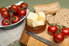 Bread and butter/Delicious organic home-made bread and butter with ripe tomatoes on wooden board. Stock Image