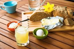 Bread, butter, egg, juice, butter, cheese on wooden table (breakfast) Royalty Free Stock Images