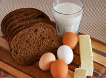 Bread, Butter, Eggs, Milk on a Cutting Board Royalty Free Stock Photo
