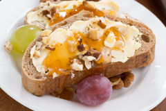 Bread with butter, honey, nuts and grapes Stock Photos