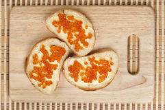 Bread, butter and red caviar Stock Images