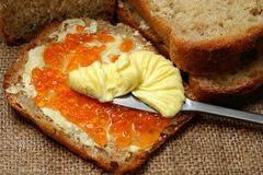Bread, Butter & Red Caviar. Thick slices of whole-wheat bread, one slice spread with red caviar, knife spreading thick yellow butter, burlap background stock photos