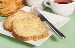 Bread and butter on square white plate and cup of herbal tea Royalty Free Stock Photos