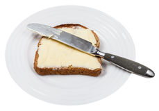 Bread and butter with table knife on white plate Stock Photography