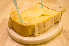 Bread butter. Bread toast and condensed milk on wooden plate Stock Images