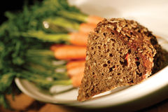 Bread Carrot. Image composition of bread on the foreground and carrot on the background royalty free stock photography