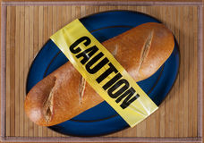 Bread with Caution Tape. Loaf of French Bread draped in Caution Tape royalty free stock image