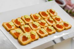 Bread with caviar on a white plate of the banquet table stock photos