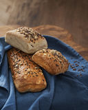 Bread with cereals and flax seeds on a linen. Bread with cereals and flax seeds on a blue linen Stock Photos