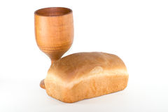Bread and chalice. A still life picture of a loaf of uncut homemade bread and a wooden chalice isolated against a white background royalty free stock photos