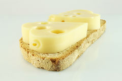 Bread and cheese. On a piece of bread, two cheese hearts Royalty Free Stock Image
