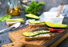 Bread with cheese and with avocado. On wooden board stock photos