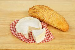 Bread and cheese. Camembert cheese and a crusty bread roll on a wooden chopping board royalty free stock images