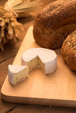 Bread and cheese. On chopping board and rustic background Stock Images