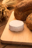 Bread and cheese. On chopping board and rustic background Stock Photo
