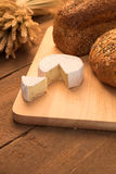 Bread and cheese. On chopping board and rustic background Royalty Free Stock Image