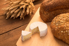 Bread and cheese. On chopping board and rustic background Stock Photos